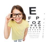 Усмехаясь маленькая девочка в eyeglasses с диаграммой глаза стоковые фото