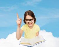 Усмехаясь маленькая девочка в eyeglasses с книгой Стоковые Изображения RF