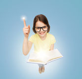 Усмехаясь маленькая девочка в eyeglasses с книгой Стоковая Фотография