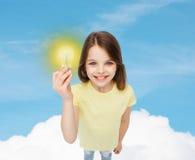 Усмехаясь маленькая девочка держа электрическую лампочку Стоковое Изображение RF