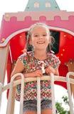 Усмехаясь маленькая девочка играя на оборудовании спортивной площадки Стоковые Фотографии RF