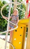 Усмехаясь маленькая девочка играя на оборудовании спортивной площадки Стоковые Изображения