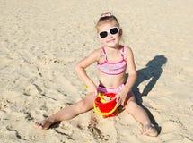 Усмехаясь маленькая девочка играя на пляже стоковые фотографии rf