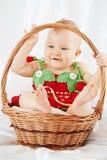 Усмехаясь маленькая девочка одела в костюме клубники сидя в корзине Стоковое Изображение