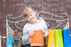 Усмехаясь маленькая девочка после ходить по магазинам Стоковое фото RF