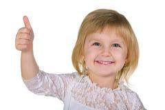 Усмехаясь маленькая девочка с ее большим пальцем руки вверх стоковые фотографии rf