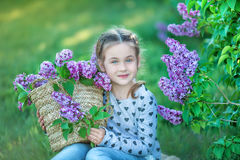 Усмехаясь маленькая милая белокурая девушка ребенка 4-9 лет с букетом сирени в руках в джинсах и рубашке стоковое изображение rf