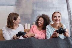 Усмехаясь маленькие девочки играя игры в спальне дома Стоковое Фото