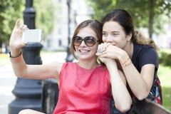 Усмехаясь маленькие девочки при сотовый телефон сидя на стенде в парке Стоковые Фотографии RF
