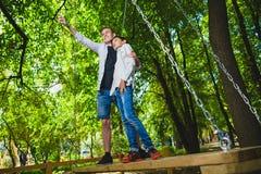 Усмехаясь мальчики имея потеху на спортивной площадке Дети играя outdoors в лете Подростки ехать на качании снаружи Стоковые Изображения