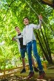 Усмехаясь мальчики имея потеху на спортивной площадке Дети играя outdoors в лете Подростки ехать на качании снаружи Стоковое Фото