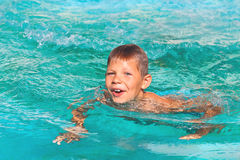 Усмехаясь мальчик в бассейне стоковое изображение