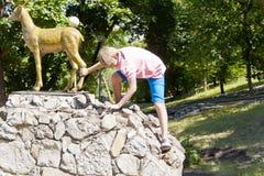 Усмехаясь мальчик в каменном парке Стоковые Изображения