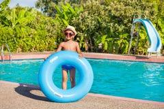 Усмехаясь мальчик в шляпе держит голубое раздувное кольцо Стоковые Изображения
