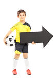 Усмехаясь мальчик в sportswear держа шарик и черное pointin стрелки стоковые фотографии rf