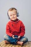 Усмехаясь мальчик закрывая его глаза пока слушающ к музыке Стоковое Изображение