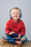 Усмехаясь мальчик закрывая его глаза пока слушающ к музыке Стоковые Фотографии RF