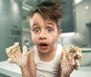 Усмехаясь мальчик замешивая тесто Стоковые Изображения RF
