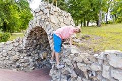 Усмехаясь мальчик играя на каменной стене Стоковое фото RF