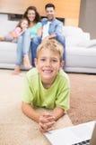 Усмехаясь мальчик используя компьтер-книжку на половике при родители сидя софа Стоковое фото RF