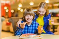 Усмехаясь мальчик и девушка есть пиццу или выпивая сок крытый Стоковые Изображения
