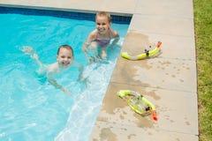 Усмехаясь мальчик и девушка играя в бассейне Стоковое Изображение RF