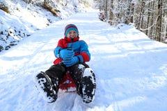 Усмехаясь мальчик наслаждается sledging Стоковые Фото