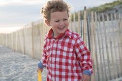 Усмехаясь мальчик на пляже перед деревянной загородкой Стоковые Изображения RF