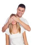 Усмехаясь мальчик покрывая глаза его подруги для того чтобы удивить его Стоковые Фото