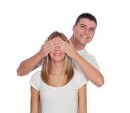 Усмехаясь мальчик покрывая глаза его подруги для того чтобы удивить его Стоковое Изображение
