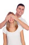 Усмехаясь мальчик покрывая глаза его подруги для того чтобы удивить его Стоковые Фотографии RF