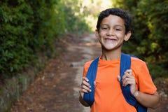 Усмехаясь мальчик при рюкзак стоя на пути в лесе Стоковая Фотография