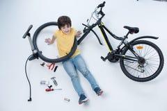 Усмехаясь мальчик сидя на поле около велосипеда на белизне Стоковые Изображения RF