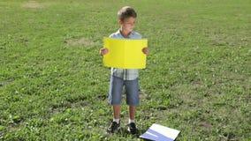 Усмехаясь мальчик стоя с пустым пустым знаменем акции видеоматериалы