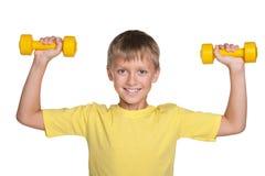 Усмехаясь мальчик с гантелями делает тренировки стоковая фотография