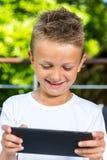 Усмехаясь мальчик с таблеткой Стоковые Фотографии RF