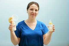 Усмехаясь медсестра держит насос груди, бутылку молока смешанный подавать, сохраняя молоковыведение работающей мамы Помощь с корм стоковые фотографии rf