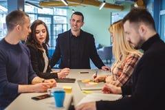 Усмехаясь менеджер смотря его коллеги на встрече офиса Стоковая Фотография