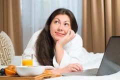 Усмехаясь мечтательная девушка с компьтер-книжкой Стоковые Фото