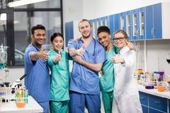Усмехаясь медицинские работники показывая большие пальцы руки вверх в лаборатории Стоковая Фотография