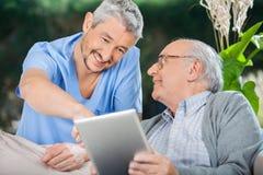 Усмехаясь медсестра помогая старшему человеку используя в таблетке