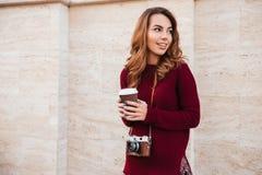 Усмехаясь милая девушка при ретро камера стоя outdoors Стоковое фото RF