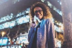 Усмехаясь милая женщина делая переговор вызывает с ее друзьями через телефон клетки пока стоящ на ноче на улице стоковое фото