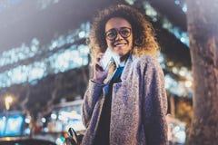 Усмехаясь милая женщина делая переговор вызывает с ее друзьями через телефон клетки пока стоящ на ноче на улице стоковая фотография