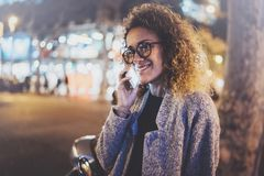 Усмехаясь милая женщина делая переговор вызывает с ее друзьями через телефон клетки пока стоящ на ноче на улице стоковые изображения rf