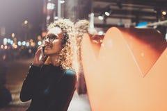 Усмехаясь милая женщина делая переговор вызывает с ее друзьями через телефон клетки пока стоящ на ноче на улице стоковые фото