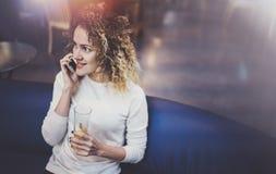 Усмехаясь милая молодая женщина делая переговор вызывает с ее друзьями через телефон клетки пока посылающ свободное время на горо стоковые фотографии rf