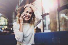 Усмехаясь милая молодая женщина делая переговор вызывает с ее друзьями через телефон клетки пока посылающ свободное время на горо стоковое фото rf