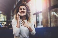 Усмехаясь милая молодая женщина делая переговор вызывает с ее друзьями через телефон клетки пока посылающ свободное время на горо стоковое изображение
