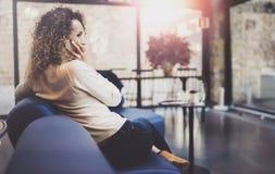 Усмехаясь милая молодая женщина делая переговор вызывает с ее друзьями через телефон клетки пока посылающ свободное время на горо стоковое изображение rf